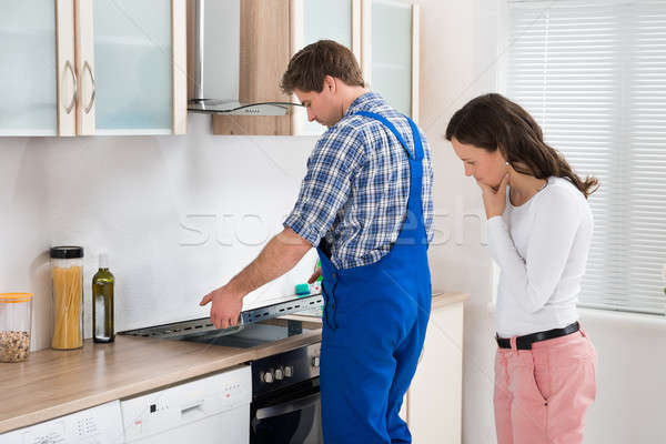 Woman Looking At Worker Repairing Induction Hob Stock photo © AndreyPopov