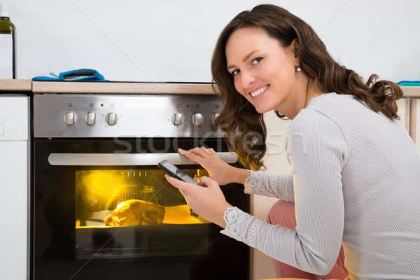 Woman With Mobile Phone While Cooking Chicken Stock photo © AndreyPopov