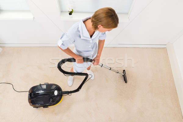 Female Maid Using Vacuum Cleaner For Cleaning Floor Stock photo © AndreyPopov