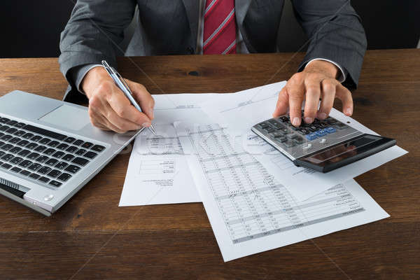 Midsection Of Businessman Checking Bills At Desk Stock photo © AndreyPopov