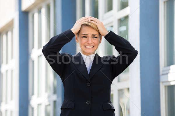 Szomorú üzletasszony kezek fej fiatal áll Stock fotó © AndreyPopov