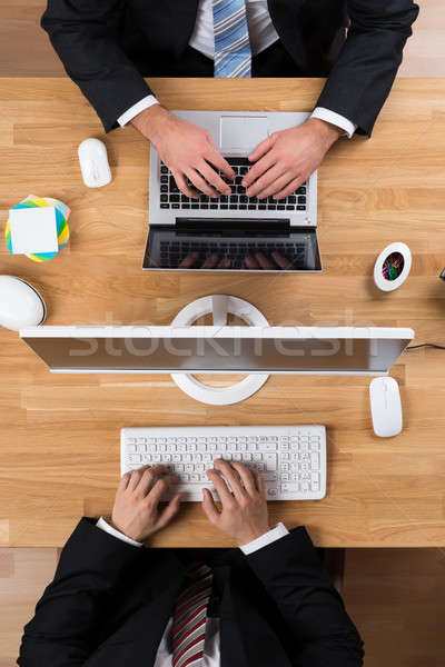 Businessmen Using Laptop And Computer At Desk Stock photo © AndreyPopov