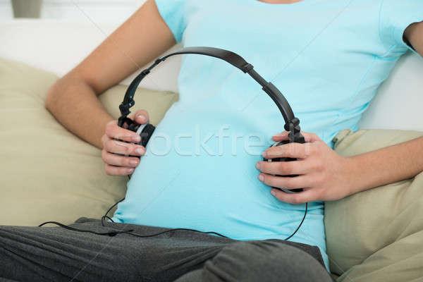 Mulher grávida fones de ouvido estômago casa música grávida Foto stock © AndreyPopov