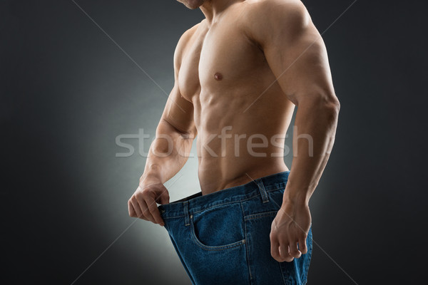 Midsection Of Muscular Man In Old Jeans Showing Weight Loss Stock photo © AndreyPopov