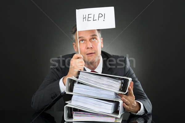 Businessman Holding Flag With Help Text Above Stack Of Folders Stock photo © AndreyPopov