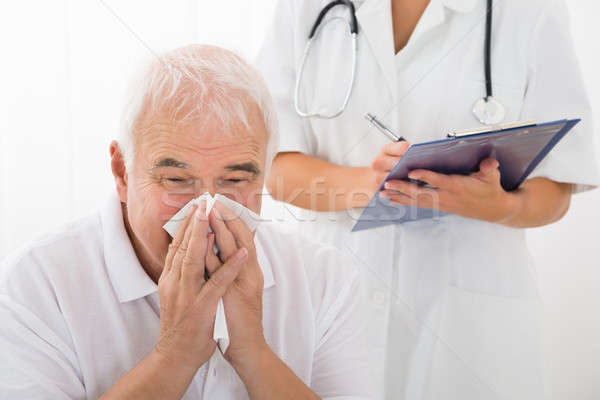 Senior Man Infected With Cold Blowing His Nose In Clinic Stock photo © AndreyPopov