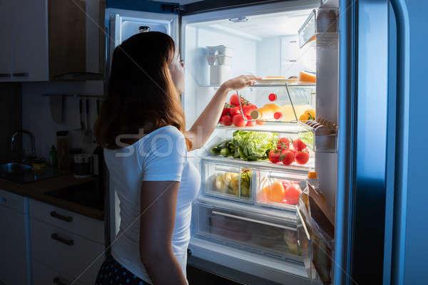 Kobieta patrząc żywności lodówce młoda kobieta otwarte Zdjęcia stock © AndreyPopov