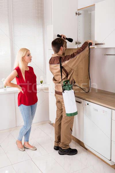 Male Worker Spraying Pesticide On Shelf In Kitchen Stock photo © AndreyPopov