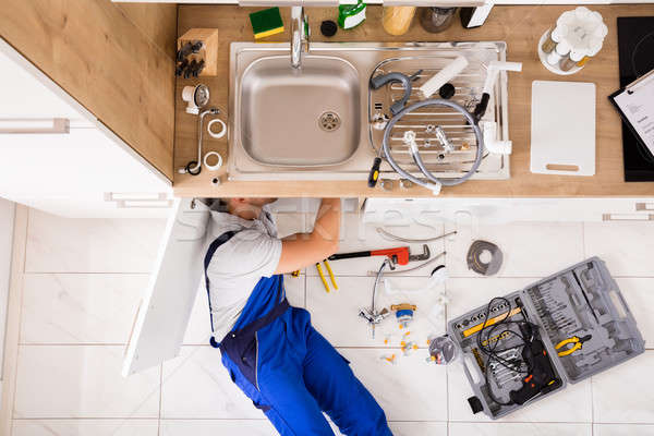 Stock photo: Male Plumber In Overall Fixing Sink Pipe