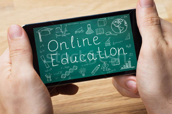 Person Holding Smart Phone Showing Online Education Stock photo © AndreyPopov