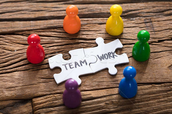 Teamwork Jigsaw Pieces Surrounded By Colorful Pawn Figurines Stock photo © AndreyPopov