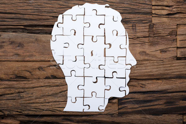Businessman's Head Made From Paper Jigsaw Puzzle Pieces On Table Stock photo © AndreyPopov