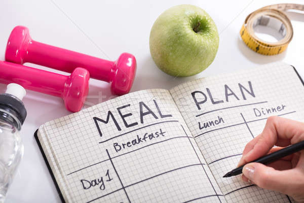 Filling Meal Plan In Notebook At Wooden Desk Stock photo © AndreyPopov