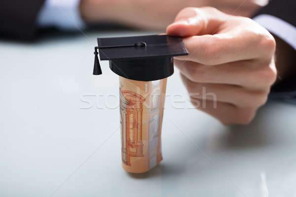 Human Hand Placing Graduation Hat Over Rolled Up Banknotes Stock photo © AndreyPopov