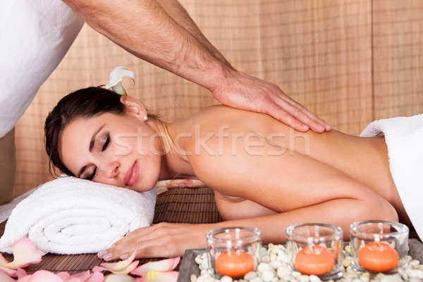 Beautiful young woman getting back massage Stock photo © AndreyPopov