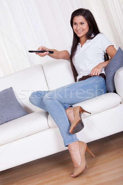 Donna sorridente telecomando seduta divano mani copia spazio Foto d'archivio © AndreyPopov