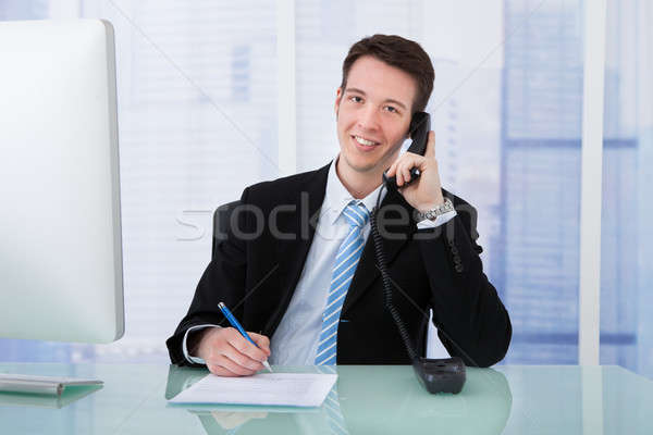 Businessman Using Telephone While Writing On Document At Desk Stock photo © AndreyPopov