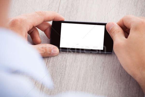 Kéz tart okostelefon képernyő közelkép asztal Stock fotó © AndreyPopov