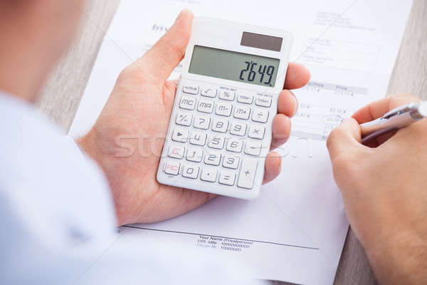 Businessman Calculating Invoice At Desk Stock photo © AndreyPopov