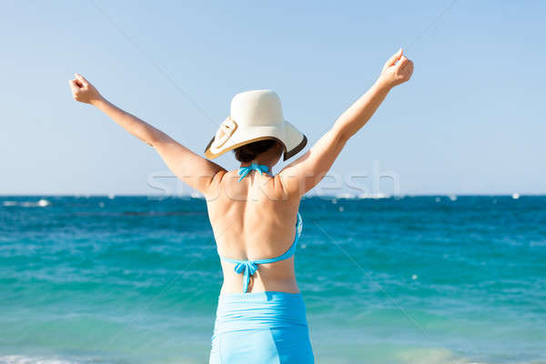 Yyoung woman standing arms raised at beach against sea Stock photo © AndreyPopov