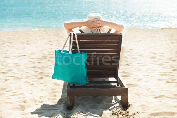 Stock photo: Woman relaxing on deck chair at beach resort
