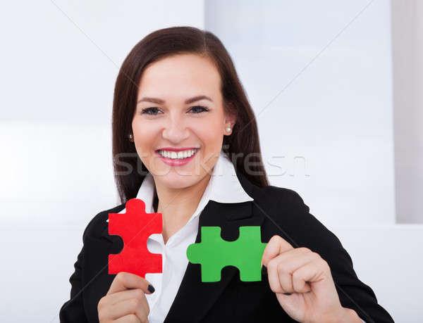 Happy Businesswoman Holding Puzzle Pieces Stock photo © AndreyPopov