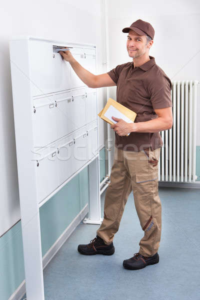 Postman Putting Letters In Mailbox Stock photo © AndreyPopov