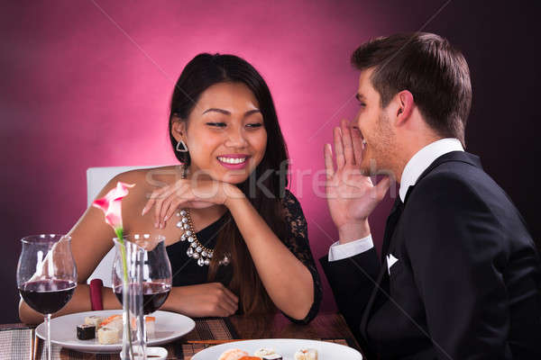 Man Whispering In Woman's Ear At Restaurant Stock photo © AndreyPopov