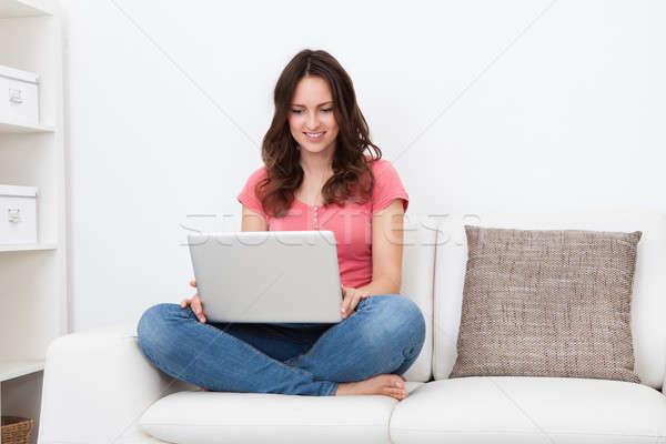 Jonge vrouw met behulp van laptop portret glimlachend vergadering bank Stockfoto © AndreyPopov