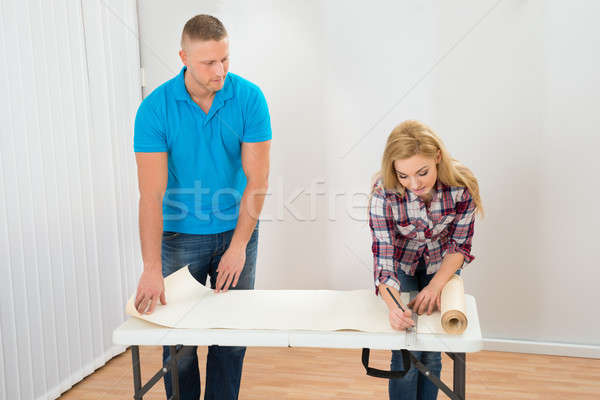Young Couple Taking Measurement Of Wallpaper Stock photo © AndreyPopov