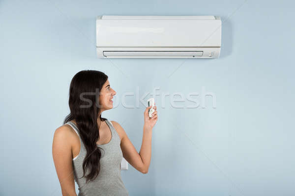 Woman With Remote Control Of Air Conditioner Stock photo © AndreyPopov