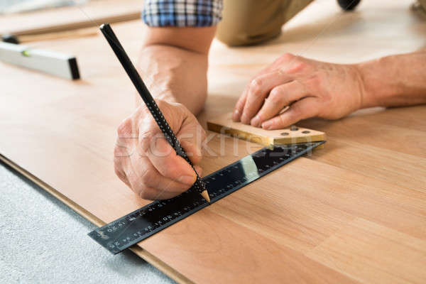 Worker Drawing A Mark On Laminate Stock photo © AndreyPopov