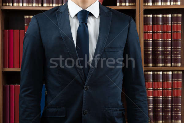 Midsection Of Lawyer Standing Against Bookshelf Stock photo © AndreyPopov