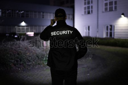 Stock photo: Security Guard Searching With Flashlight In Office