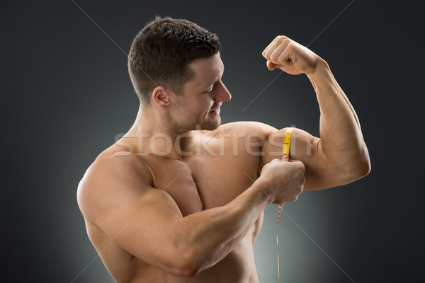 Happy Muscular Man Measuring Bicep With Measure Tape Stock photo © AndreyPopov