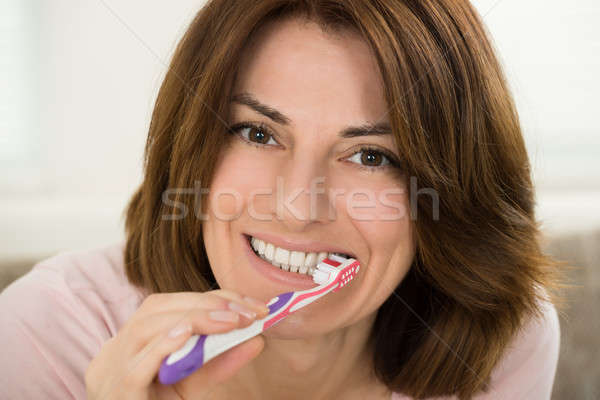 Young Woman Brushing Her Teeth Stock photo © AndreyPopov