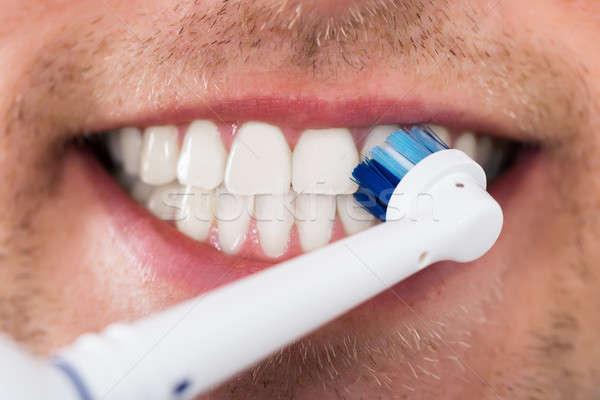 Hombre dientes eléctrica cepillo de dientes primer plano joven Foto stock © AndreyPopov