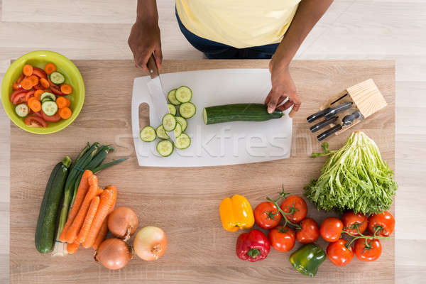 Young African Woman Chopping Vegetables In Kitchen Stock photo © AndreyPopov