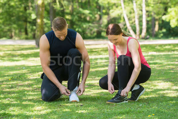 Young Couple Tying Shoes Stock photo © AndreyPopov