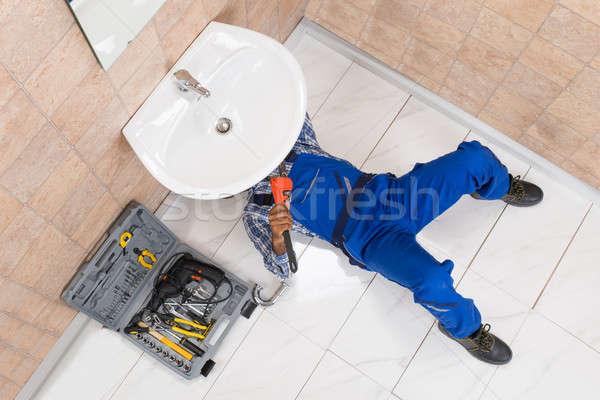 Plumber Lying On Floor Repairing Sink In Bathroom Stock photo © AndreyPopov