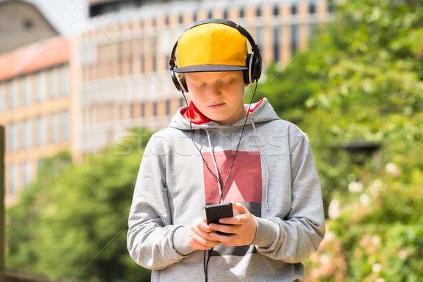Boy Wearing Yellow Cap Listening To Music Stock photo © AndreyPopov