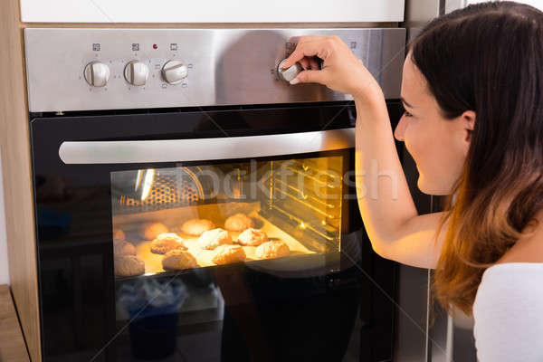 Woman Using Microwave Oven In Kitchen Stock photo © AndreyPopov