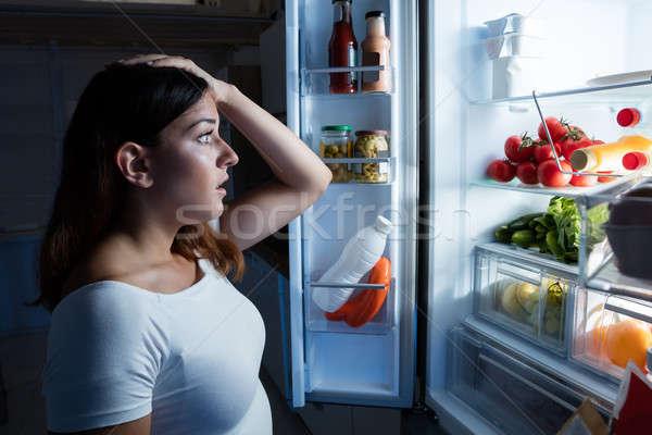 Mujer mirando abierto refrigerador jóvenes confundirse Foto stock © AndreyPopov