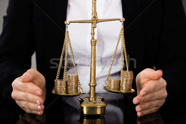 Lawyer's Hand Protecting Justice Scale With Coins Stock photo © AndreyPopov