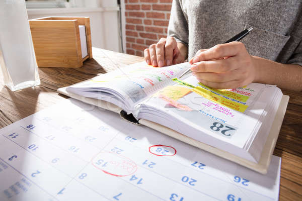 Businesswoman Marking Schedule On Calendar Stock photo © AndreyPopov
