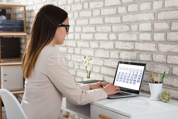 Işkadını bakıyor takvim dizüstü bilgisayar yazarak laptop klavye Stok fotoğraf © AndreyPopov