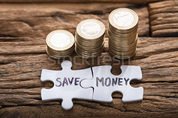 Save Money Jigsaw Pieces By Stacked Coins Stock photo © AndreyPopov