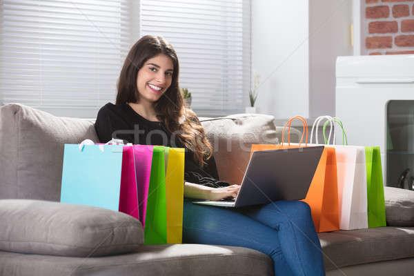 Foto stock: Feliz · mujer · usando · la · computadora · portátil · sesión · sofá