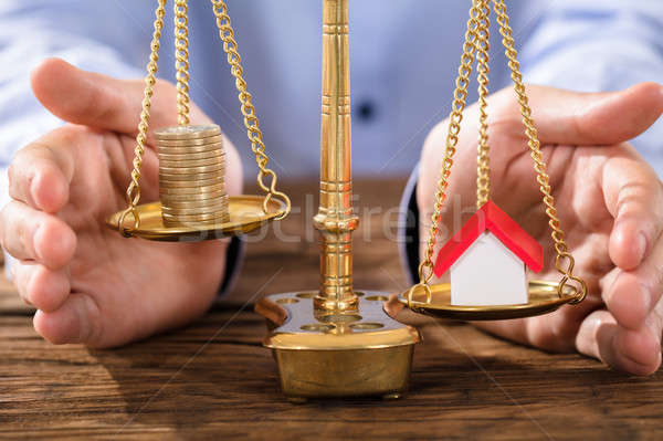 Person Protecting Justice Scale With Coins And House Model Stock photo © AndreyPopov
