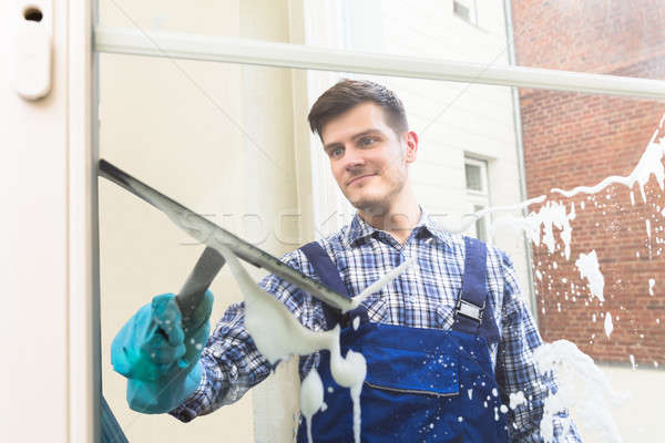 Housekeeper Cleaning Window With Squeegee Stock photo © AndreyPopov
